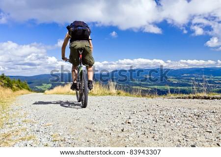 Mountain biking in summer mountains, man riding a bike in summer nature - stock photo
