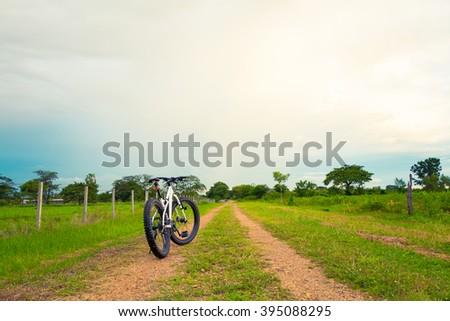 Mountain biking on single track beautiful nature green grass and cloud blue sky - stock photo