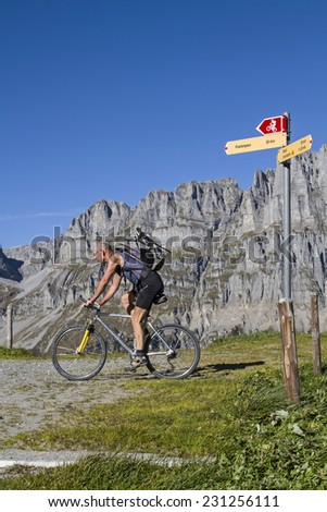 Mountain biking with signpost for climbers and mountain bikers in the Urner Alps - stock photo