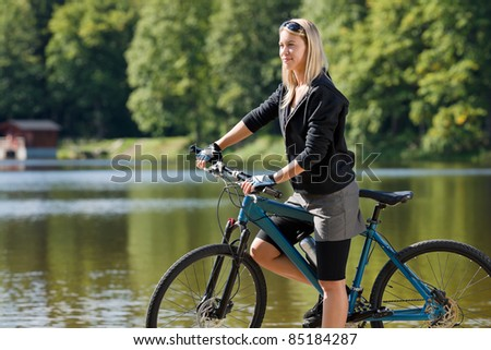 Mountain biking young woman standing on pier looking natural lake - stock photo