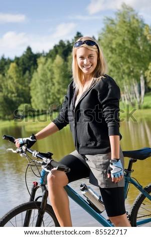 Mountain biking young woman standing on pier looking natural lake - stock photo