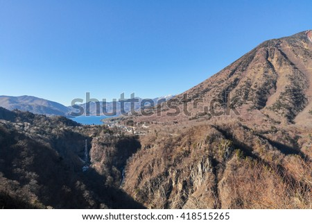 Mountain, blue lake (Lake Chuzenji), great falls (Kegon waterfall) under blue sky. Photo taken from Akechi-daira observatory, Nikko National Park, Tochigi Prefecture, Japan. - stock photo