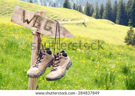 Mountain boots hanging on a signpost