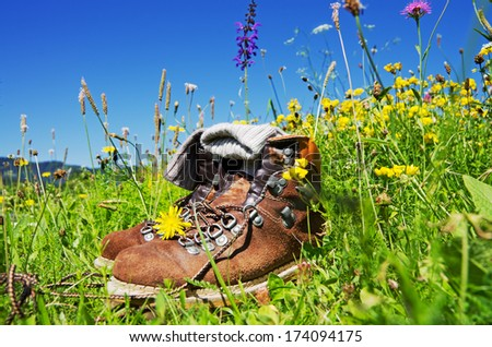 mountain boots on alpine pasture with blue sky - stock photo