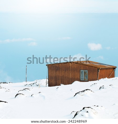 mountain building on sky and snow background - stock photo