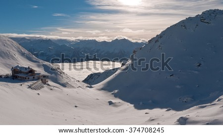 Mountain caf�© above the clouds. With the ski slopes can be seen cozy restaurant above the valley, which is covered by clouds. The sun illuminates the top of the mountain. December 30, 2010: Austria, - stock photo