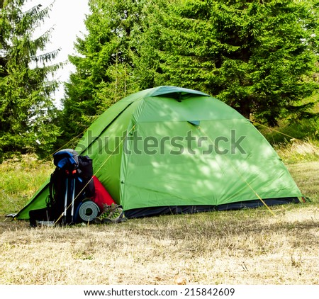Mountain Camping Equipment with Boots ,Backpack and Tent on Nature Background with Fir Trees - stock photo