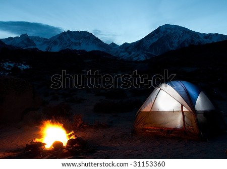 Mountain Campsite at Night with Tent and Fire - stock photo