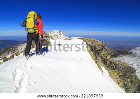 Mountain climber ascending with an ice axe in winter - stock photo