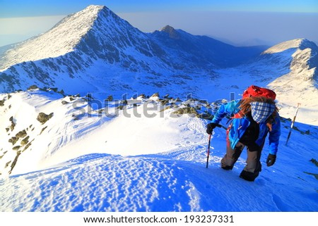Mountain climber ascends snow covered slope in sunny day - stock photo
