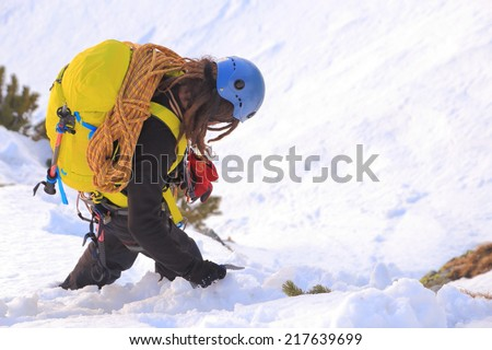 Mountain climber carries a backpack and climbing gear on snowy trail - stock photo