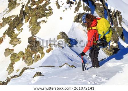 Mountain climber descending on narrow ridge in winter  - stock photo