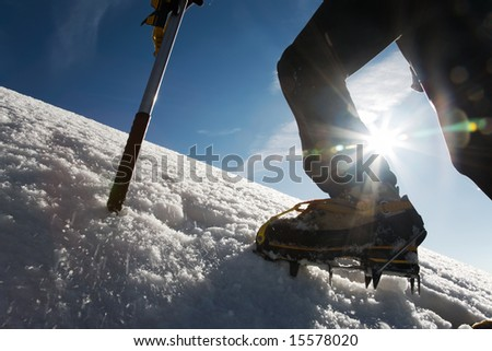 Mountain climber: detail on boot with ice crampon and ice axes; back-light - stock photo