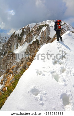Mountain climber in bad weather during winter - stock photo