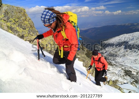 Mountain climbers on a steep route in winter - stock photo