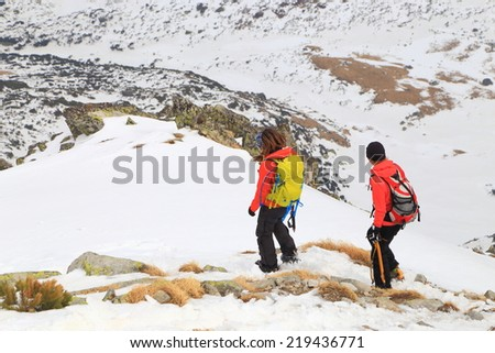 Mountain climbers walking on a snow covered mountain - stock photo