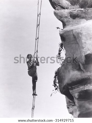 Mountain climbing by ladder - stock photo