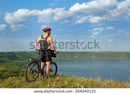 Mountain cyclist stands on the shore of the beautiful Reservoir Bakota. Ukraine