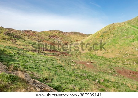 Mountain desert with fresh spring green grass. Mountain plain field / meadow with nice round hills and red soil. Madeira Island, Portugal. - stock photo