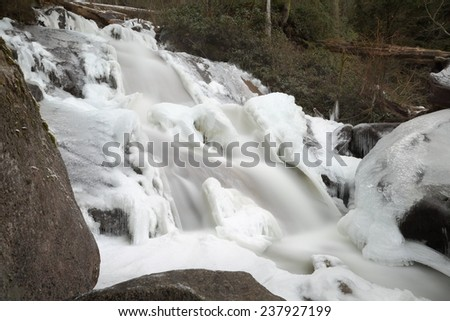 Mountain Falls, Winter Ice. Long exposure of a mountain stream waterfall with ice and snow. Motion blur.  - stock photo