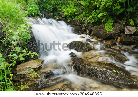 Mountain fast flowing river stream of water in the rocks - stock photo