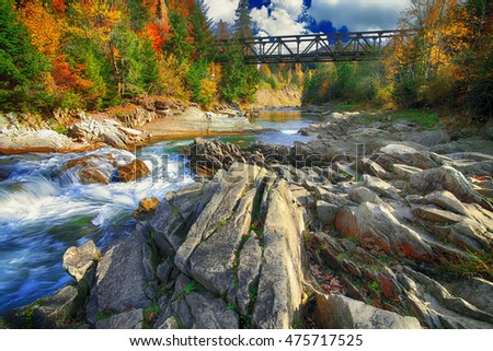 Mountain fast flowing river stream of water in the rocks with blue sky at autumn time. Colorful foliage. Railway bridge.