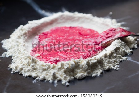 Mountain flour with deepening, beet juice  and egg, making homemade pasta - stock photo