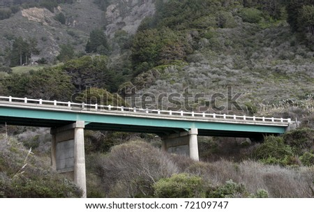 mountain highway  bridge spans two mountains with rocks and trees as a background