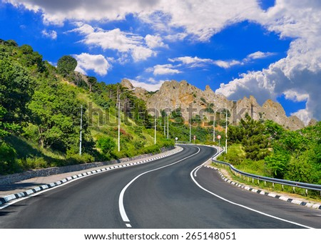 Mountain highway winds among mountain ranges against the blue sky - stock photo
