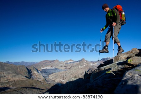 Mountain hiker with backpack high in the mountains - stock photo
