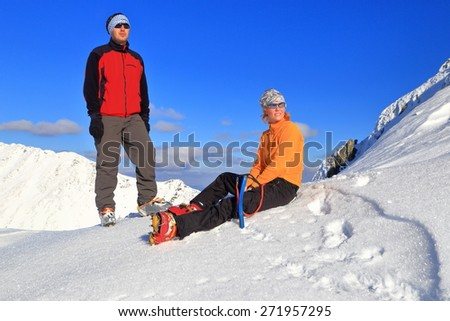 Mountain hikers resting on the snow during fine winter day - stock photo