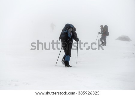 Mountain hiking group with backpacks and trekking poles having hard climbing trip in winter snow storm - stock photo