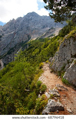 mountain hiking trail in alps on a sunny day in slovenia - stock photo