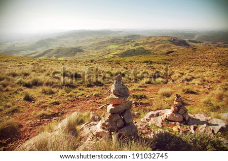 Mountain hiking trail with stone piles or cairns marking the way - stock photo