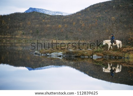 Mountain horse rider, Sami reindeer herder, in the Vindelfjallen nature reserve, Vasterbotten, Lappland, Ammarnas, Sweden - stock photo