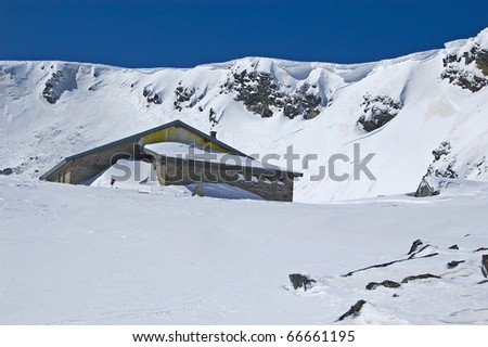 Mountain house in the snow at sunny day