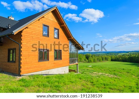 Mountain house on green field in countryside of Beskid Niski Mountains on sunny day, Poland