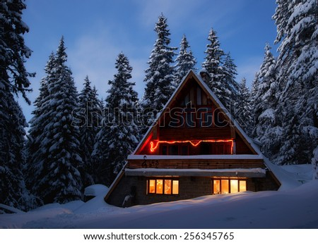 Mountain hut in winter evening - stock photo