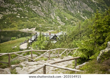 Mountain hut surrounded by hills, mountains and conifers during summer, cloudy day. From the top. - stock photo
