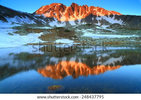 Mountain illuminated at sunset and reflected by glacier lake - stock photo