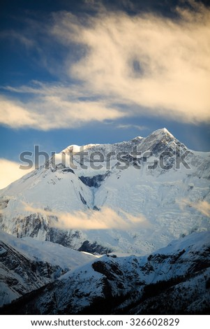 Mountain inspirational landscape in Himalayas, Annapurna range, Nepal. Mountain ridge with ice and snow over clear blue sunny sky. - stock photo