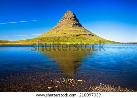 Mountain Kirkjufell and its reflection in the water. Grundarfjordur, Snaefellsnes peninsula, Western Iceland