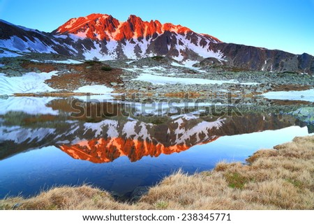 Mountain lake and distant summits illuminated by the rising sun - stock photo