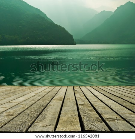 Mountain lake and flowing river with a wooden bridge - stock photo