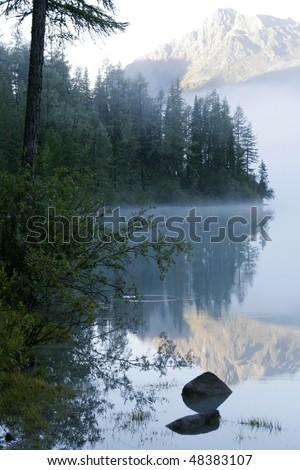 Mountain lake and fog - stock photo