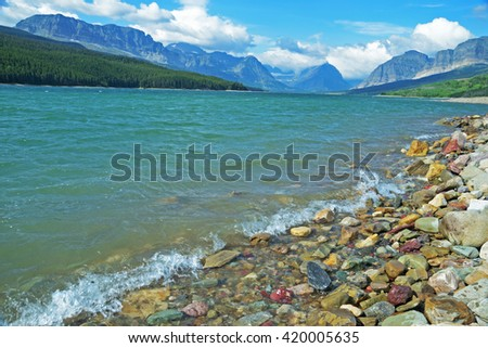 Mountain lake, and shoreline in Glacier National Park. - stock photo
