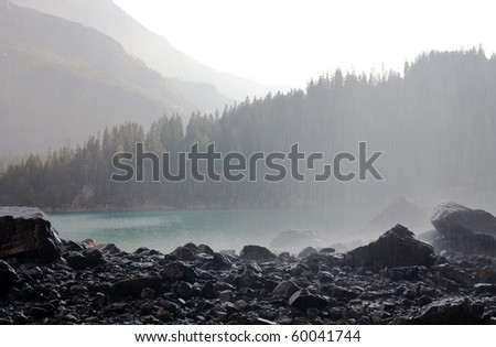 mountain lake and waterfall on foreground - stock photo