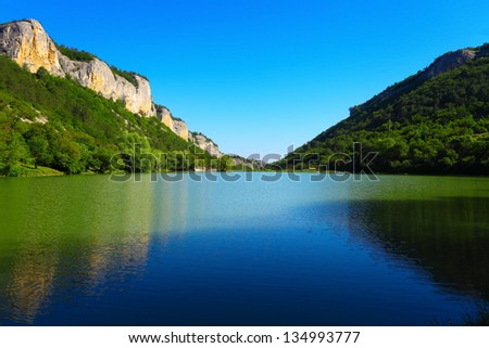 Mountain lake between the rocks and green trees. Tranquil summer landscape