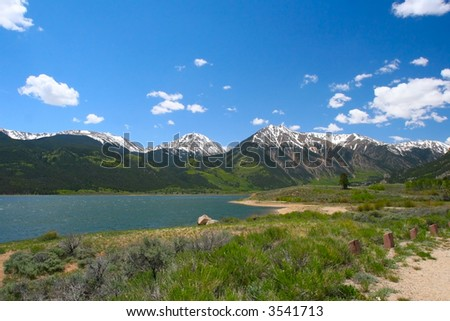 Mountain Lake in Springtime reflects the brilliant blue sky and contrasts with the bright green new leaf growth on the snow-capped peaks. - stock photo