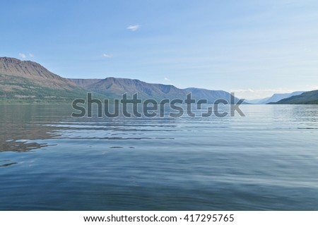 Mountain lake in the morning. Summer wild landscape water lake on the Putorana Plateau